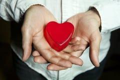 Mens die een rood hart in handen houdt Royalty-vrije Stock Fotografie