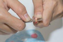 Mens die een rood potloodkleurpotlood scherpen Stock Afbeeldingen