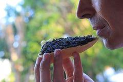 Mens die een sandwich met zwarte kaviaar eten Stock Afbeeldingen