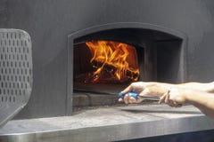Mens die een Schil van de Metaalpizza gebruiken aan het koken het bakken in openlucht in een staal houten brandende oven voor piz stock foto's