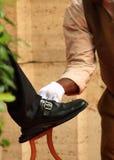 Mens die een schoen oppoetst stock afbeelding