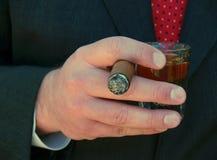 Mens die een sigaar en een schot van whisky houdt Stock Fotografie