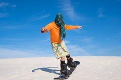 Mens die een sjaal belast met het snowboarding in woestijn dragen royalty-vrije stock afbeeldingen