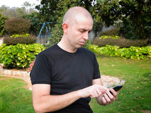 Mens die een slimme telefoon met behulp van Stock Foto