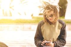 Mens die een slimme toegepaste filter met behulp van van telefoon in openlucht warme tonen Royalty-vrije Stock Foto's