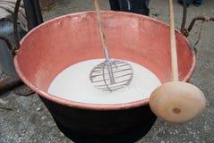 Mens die een speciale gietlepel en koperketel gebruiken die melk bevatten die kaas worden royalty-vrije stock foto's
