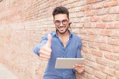 Mens die een stootkussencomputer houden en het o.k. teken maken royalty-vrije stock afbeeldingen