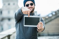 Mens die een tablet houden en op het scherm richten - vage achtergrond Stock Afbeeldingen