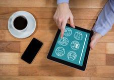 Mens die een tablet met reispictogrammen houden op het scherm Stock Fotografie