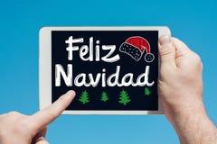 Mens die een tabletapparaat met tekst in Spaanse ` Feliz Navidad Merry Christmas en wat betreft het scherm houden stock foto