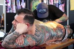 Mens die een tatoegering krijgen, bij een tatoegeringsstudio royalty-vrije stock afbeeldingen