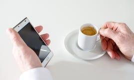 Mens die een telefoon en een koffie houden Stock Foto's