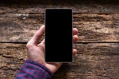 Mens die een telefoon in zijn hand op de houten achtergrond houden Royalty-vrije Stock Afbeelding