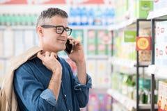 Mens die een telefoongesprek hebben bij de supermarkt stock afbeelding