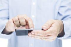 Mens die een touchscreen mobiele telefoon in werking stellen Stock Fotografie