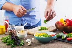 Mens die een vegetarische salade maken stock afbeelding