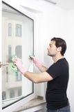 Mens die een venster schoonmaakt Stock Fotografie