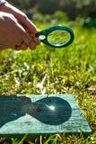 Mens die een vergrootglas houden die brand maken, die op hout wordt geconcentreerd stock foto