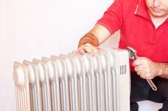 Mens die een verwarmer herstellen Stock Foto's