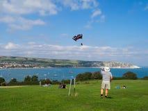 Mens die een vlieger op heuvel boven Swanage-Baai vliegen Stock Fotografie