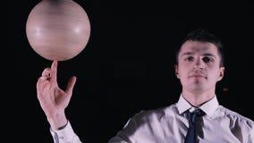 Mens die een voetbalbal op zijn vinger spinnen stock footage