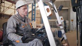 Mens die een vorkheftruck drijven door een pakhuis in een fabriek bestuurder in eenvormige en beschermende helm Het concept van stock videobeelden