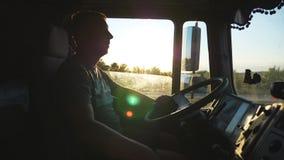 Mens die een vrachtwagen drijven en zorgvuldig op de weg letten De Kaukasische kerel berijdt door het platteland op de zonsonderg stock video