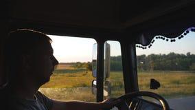 Mens die een vrachtwagen drijven en zorgvuldig op de weg letten De Kaukasische kerel berijdt door het platteland op de zonsonderg stock footage