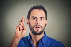 Mens die een wens maken die zijn vingers kruisen royalty-vrije stock foto