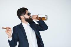 Mens die een whisky houden en van de fles drinken royalty-vrije stock foto's
