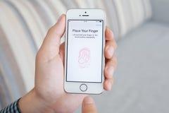 Mens die een witte iPhone 5s met Aanrakingsidentiteitskaart houden op het scherm Royalty-vrije Stock Foto's