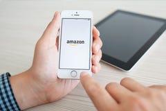 Mens die een witte iPhone 5s met app Amazonië op het scherm uitstellen Royalty-vrije Stock Afbeeldingen