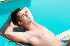 Mens die een zonbad heeft dichtbij een zwembad royalty-vrije stock afbeelding