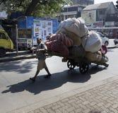 Mens die een zware geladen kar, Mumbai trekt Royalty-vrije Stock Afbeeldingen