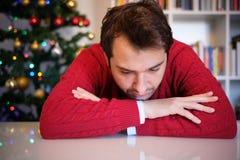 Mens die in eenzaamheid slecht tijdens Kerstmisdag voelen stock foto