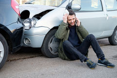 Mens die eerste hulp na autoneerstorting roepen Royalty-vrije Stock Afbeelding