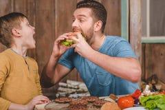 Mens die eigengemaakte hamburger met weinig dichtbij langs zoon eten royalty-vrije stock afbeeldingen