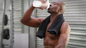 Mens die eiwitschok drinken bij crossfitgymnastiek stock videobeelden
