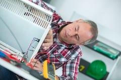 Mens die elektronisch meetinstrument om verwarmer met behulp van te bevestigen stock afbeeldingen