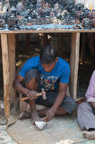 Mens die en de standbeelden van Boedha op de markt maken verkopen Stock Foto