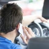 Mens die en door slimme gevaarlijke telefoon drijven spreken, stock fotografie