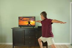 Mens die en op aan de video van de yogaklasse op TV of Internet thuis letten deelnemen Stock Foto's
