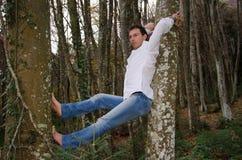Mens die en op boom denken ontspannen Stock Afbeeldingen