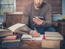 Mens die en slimme telefoon thuis bestuderen met behulp van Stock Afbeelding