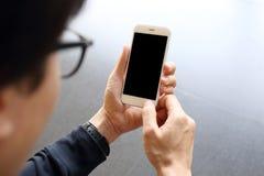 Mens die en smartphone hloding gebruiken Royalty-vrije Stock Afbeelding