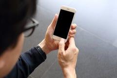 Mens die en smartphone hloding gebruiken Stock Foto
