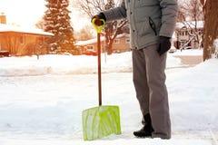 Mens die en sneeuw voor zijn huis in de voorstad scheppen verwijderen royalty-vrije stock afbeeldingen