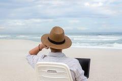 Mens die en telefoongesprekken werken nemen terwijl op het strand stock afbeeldingen