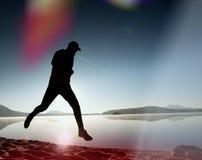 mens die en zich op het meerstrand bij zonsopgang uitoefenen uitrekken Gezonde Levensstijl De alleen jonge oefening van de geschi Stock Afbeeldingen