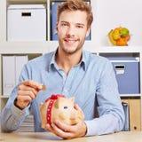 Mens die Euro geld in spaarvarken besparen Stock Foto's